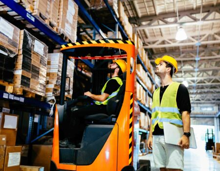 Warehouse workers working together with forklift loader trasnporter